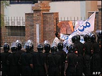 Riot police watch a man putting up a banner outside Judges Syndicate