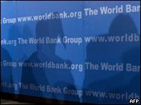 Sombras sobre una pared con carteles del Banco Mundial