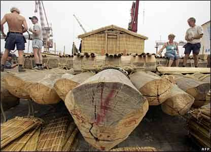 Explorers work on the construction of a wooden raft in Callao, Peru