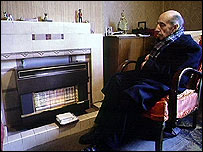An elderly man sits in front of a gas heater