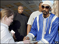 Snoop Dogg signing an autograph as he leaves London