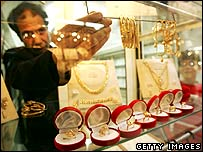 Man sets out jewellery in window of gold shop
