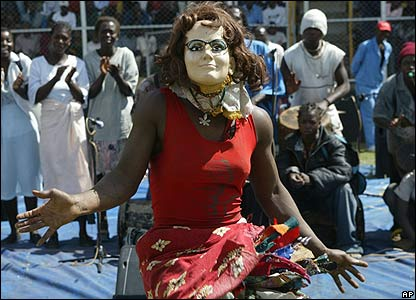 A masked Nyau dancer performs at a May Day rally in Harare, Zimbabwe