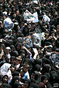 Iranian women hold up posters of Mr Ahmadinejad during a rally