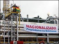 A soldier holds the Bolivian flag aloft at the Carapari gas plant in Tarija, southern Bolivia, next to a banner reading: Nationalised - property of the Bolivians