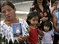 A mother holds a photograph of her murdered daughter