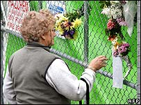 A woman inspects flowers left for two Australian miners trapped underground for more than a week