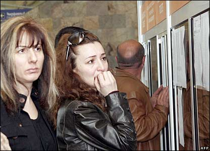 Women at Yerevan's airport read the passenger list of those killed in the crash