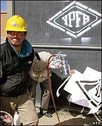 A worker applies the Bolivian energy firm's logo to seized foreign-owned premises in El Alto