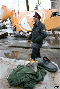 A policeman passes between the tail of the Armavia Airbus A320 plane and some belongings of the dead passengers at the dock of the port in Sochi