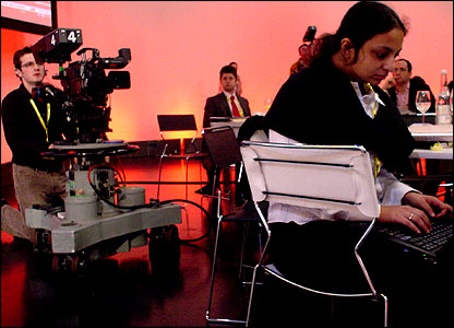 A cameraman and a woman using a laptop