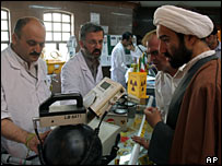 Iranian technicians explains a piece of equipment to a clergyman during an exhibition of Iran's Atomic Energy Organization at the Qom University