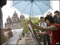 Girls do sketches outside the Wangfujing Catholic Church in Beijing