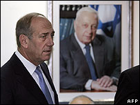 Ehud Olmert, in front of a portrait of Ariel Sharon