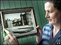Karen Gray, manager of Georgian Antiques, holds one of the photographs