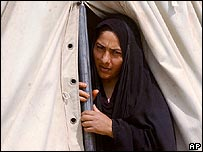 An Iraqi woman looks out of her tent at a refugee camp