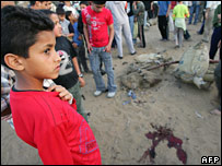 A boy looks at a blood stain at the site of the strike