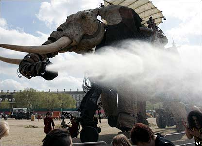 The elephant cools down some the crowd on a warm day in London