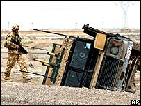 A British soldier inspects an overturned military vehicle in Basra