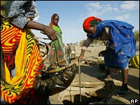 Sudanese refugees collect water at a camp in Bahai in Chad