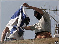 Masked settler youths try to set alight to the Israeli flag on the top of the house occupied by Jewish settlers in Hebron