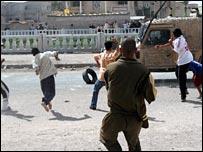 Iraqi youths throw rocks at a British military vehicle