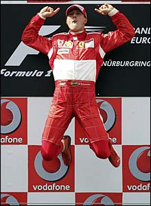 Michael Schumacher jumps for joy at the top of the podium