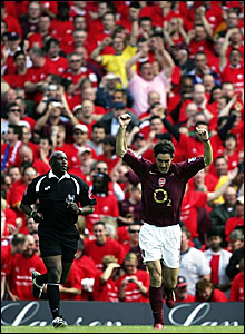 Robert Pires celebrates his goal in front of a bank of Arsenal fans decked out in free commemorative t-shirts