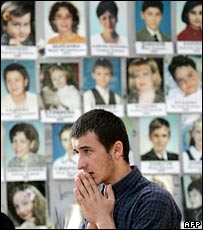 A man stands in the school gym in front of a wall of photographs of the victims one year on from the siege