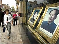 Woman passing shop with portraits of Chairman Mao