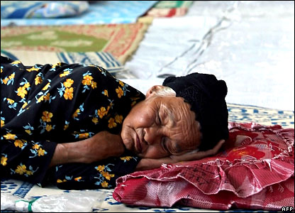 An elderly woman asleep at a refugee camp