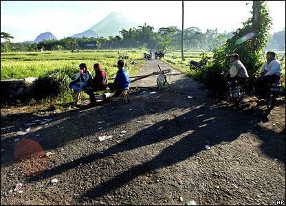 Villagers relax with Mount Merapi in the background