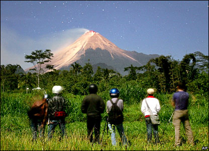 Tourists look at Mount Merapi in the distance
