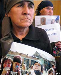 Relatives of those killed in the Beslan siege hold pictures and placards during the trial on 16 May 2006
