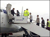 Immigrants board a plane