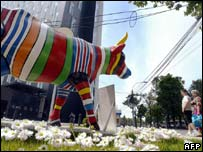 Romanian people pass nearby a plastic cow painted in the colours of EU members' national flags, in Bucharest, 15 May 2006.