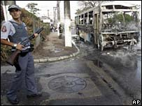 Police officer guards a burned out bus in Sao Paulo