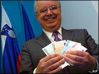 Slovene Finance Minister Andrej Bajuk holds up euro notes
