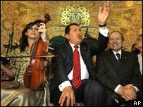 El presidente de Venezuela, Hugo Chávez, entona una canción. A su lado, sonríe su homólogo argelino