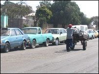 Man pushes cart past queue for petrol