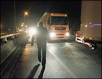 Immigrant walking past a lorries in Calais, France