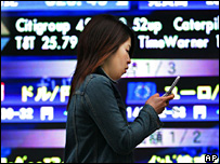 Woman walks in front of Japanese electronics stocks board
