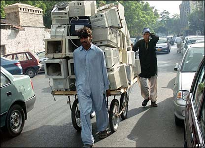 A Pakistani man pulling a cart piled with computer monitors
