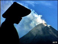 A man silhouetted against a smoking Mt Merapi