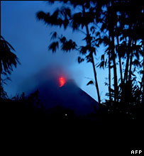 Lava gleams at the top of a distant Mt Merapi