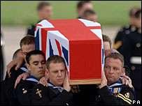 A coffin draped in the Union flag is carried across the airfield