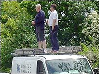 Enthusiasts stand on a van to get a better view