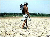 Farmer walks across parched land in northern India