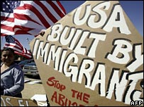 Pro-immigration activists in Arizona hold a banner and a US flag