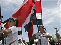 Costa Rican students march in a parade in front of the statue of national hero Juan Santamaria